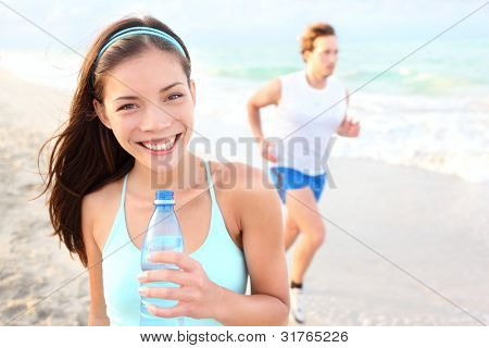 Runner woman drinking on beach with man running in background. Happy smiling mixed race Asian / Caucasian female fitness sport model during outdoor workout.