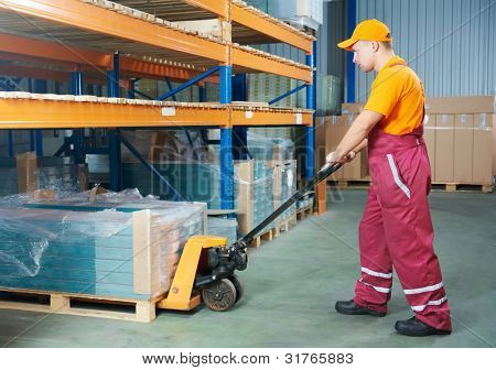 worker with fork pallet truck stacker in warehouse loading furniture panels