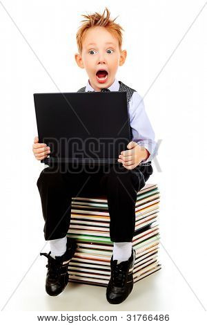 Shot of an emotional boy learning with his books and laptop. Isolated over white background.