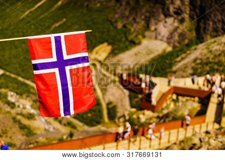 poster of Trollstigen Mountain Road Landscape In Norway, Europe. Norwegian Flag Waving And Many Tourists Peopl