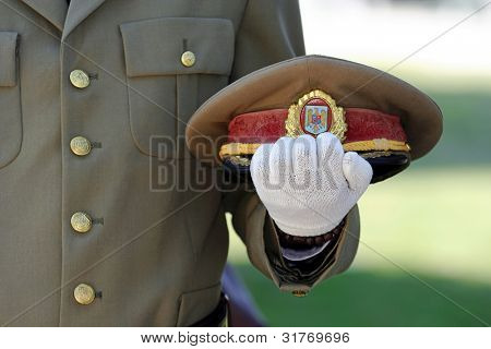 man in military field uniform with hat saluting during ceremony