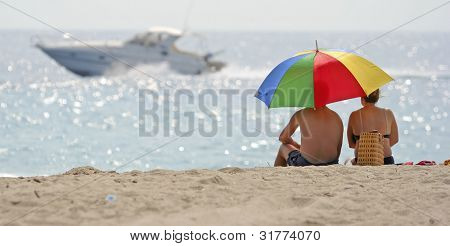 Couple sitting close together on beach looking out at ocean.
