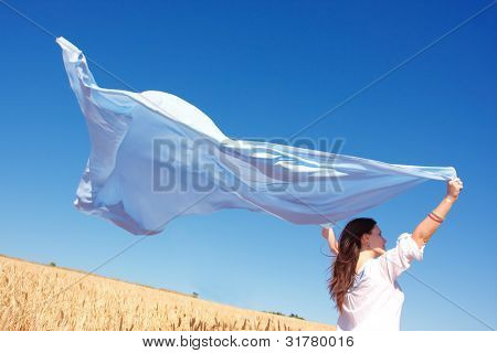 Freedom, young woman with  blue shawl in grain field
