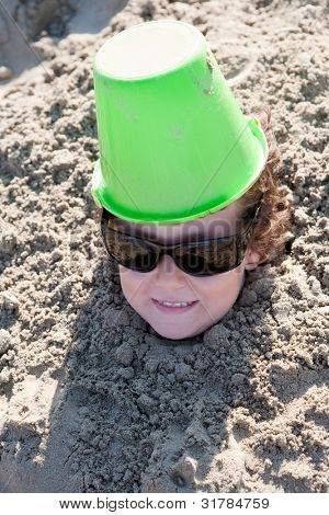Small child buried in the sand of the beach with sunglasses