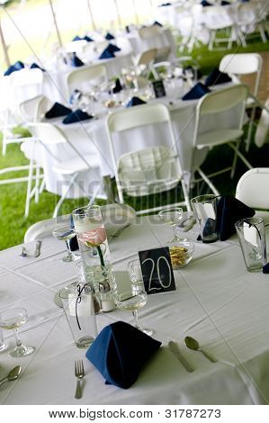wedding tables set up for fine dining under a tent