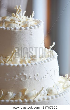 white ocean themed wedding cake with miniature seashell design and details