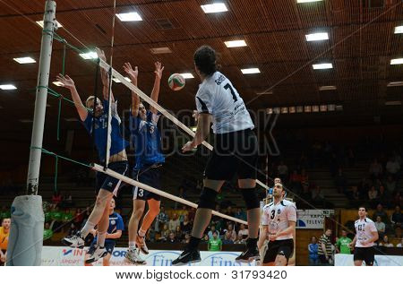 KAPOSVAR, HUNGARY - MARCH 16: Andras Geiger (white 7) in action at a Hungarian Championship volleyball game Kaposvar (white) vs. Kazincbarcika (blue), March 16, 2012 in Kaposvar, Hungary.
