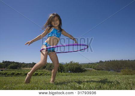 Portrait of girl in bikini playing with hoola hoop