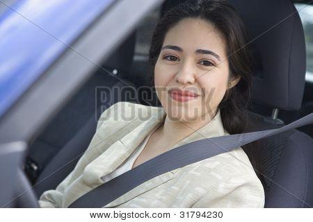 Portrait of woman sitting in car wearing seatbelt