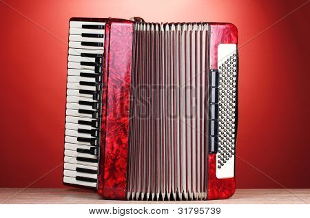 Retro accordion on wooden table on red background