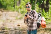 Hipster Young Man With Backpack Using Smart Phone On Beautiful Nature.travel Concept. Outdoor Travel poster