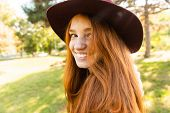 Image of positive cheerful happy young student redhead girl in autumn park walking. poster