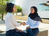 Cheerful Female Business Partners Shaking Hands Outside. Women In Office Suits And Hijab Discussing  poster