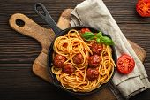 Top View Of Delicious Pasta With Meatballs, Tomato Sauce And Fresh Basil In Cast Iron Rustic Vintage poster