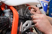 Motorcyclist Replaces, Checks The Glow Plug In A Motorcycle. poster