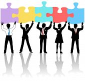 stock photo of jigsaw  - Team of business people collaborate holding up jigsaw puzzle pieces as a solution to a problem - JPG