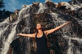 Beautiful Young Girl With Arms Raised Standing Near Waterfall At Sunset poster