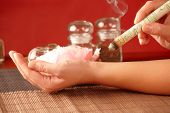 TCM Traditional Chinese Medicine. Hand applying moxa stick therapy, natural herbs in glass jars in background poster