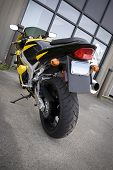 pic of crotch-rocket  - The rear view of a modern yellow motorcycle. ** Note: Slight blurriness, best at smaller sizes - JPG