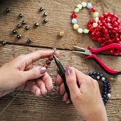 Jewelry Making. Making Bracelet Of Colorful Beads. Female Hands With A Tool On A Rough Wooden Table. poster