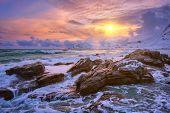 Waves of Norwegian sea on rocky coast in fjord on sunset with sun. Skagsanden beach, Lofoten islands poster