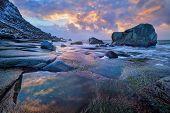 Rocks on beach of fjord of Norwegian sea in winteron sunset. Utakliev beach, Lofoten islands, Norway poster