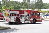 stock photo of firehose  - A bright red fire truck on duty in a parking lot - JPG