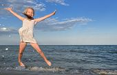 Child Girl On Summer Beach. Cheerful Little Girl Jumping And Hovering In The Air On The Background O poster