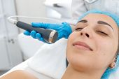 Beautician Procedure Ultrasound Fonoforeza Patient Face. A Young Girl Is Undergoing A Course Of Spa  poster