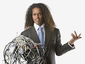 picture of adversity humor  - Businessman holding tangled computer cords - JPG