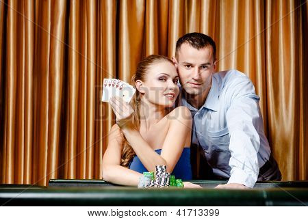 Young couple playing poker at the casino. Woman keeps cards in hand