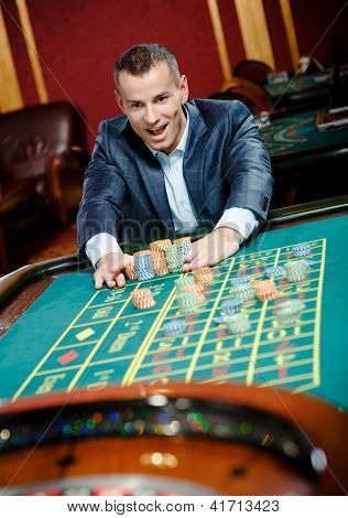 Joyful gambler stakes playing roulette at the casino. Risky entertainment of gambling