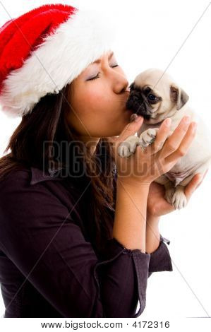 Female With Christmas Hat And Kissing Puppy