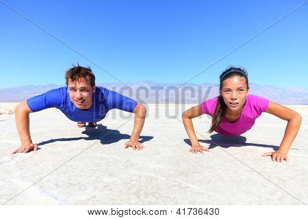 Sport - young fitness couple athletes doing push ups outdoors in desert nature landscape. Caucasian man sports model and Asian woman fitness model doing push-ups exercise under the burning sun.