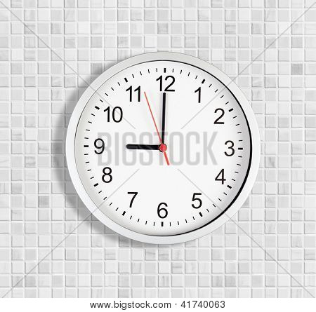 Simple clock or watch on white tile wall displaying nine o'clock