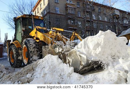 Tractor removes snow on city street