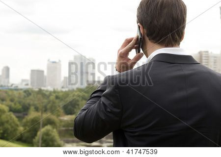 Businessman Holding The Phone Standing In Front The Major Cities