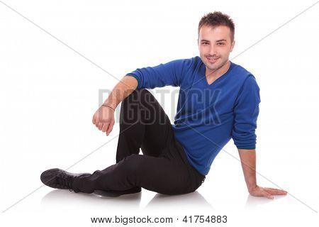 Flirtatious casual man sitting on the floor - white background