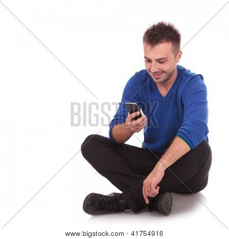 happy casual young man sitting and texting on his smartphone on white bacground