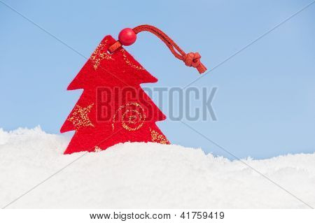 christmas tree toy in snow on sky background