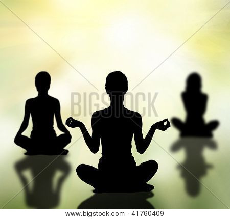 silhouettes of three women practicing yoga lotus pose