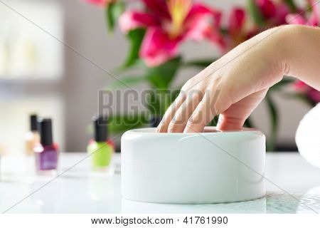 Woman in a nail salon receiving a manicure, she is bathing her hands
