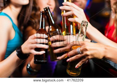Group of party people - men and women - drinking beer in a pub or bar