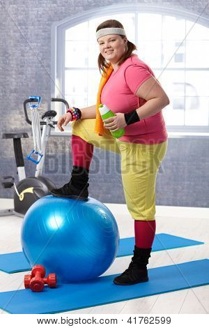 Young fat woman taking a break at the gym, resting leg on fit ball, drinking water.