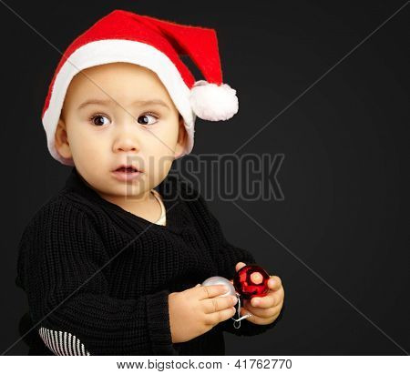 Baby Boy Wearing Santa Hat Holding Christmas Ornaments against a black background