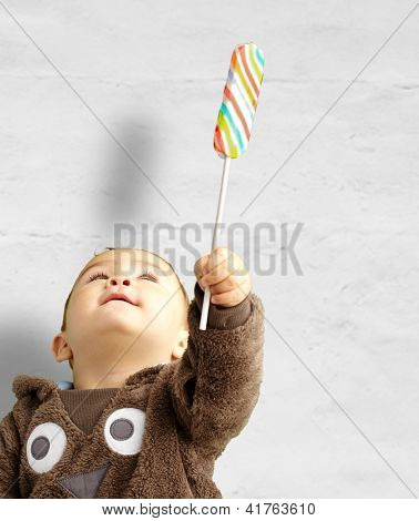 Portrait Of Baby Boy Holding Lollipop against a grunge background