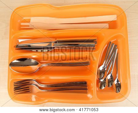 Orange plastic cutlery tray with checked cutlery on wooden table