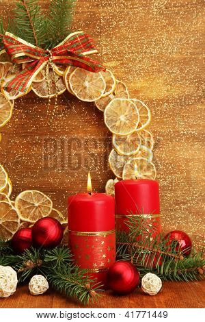 Two candles and christmas decorations, on golden background