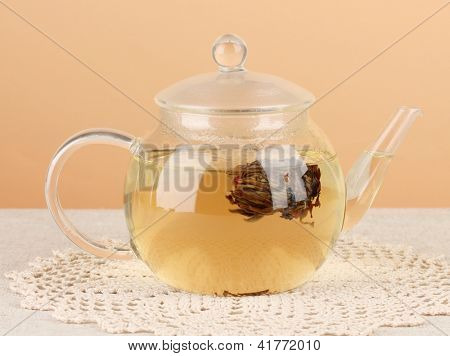 Exotic green tea with flowers in glass teapot on table on color background.Process of making tea