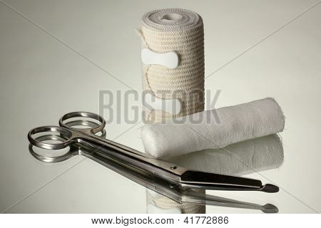 First aid kit for bandaging on grey background